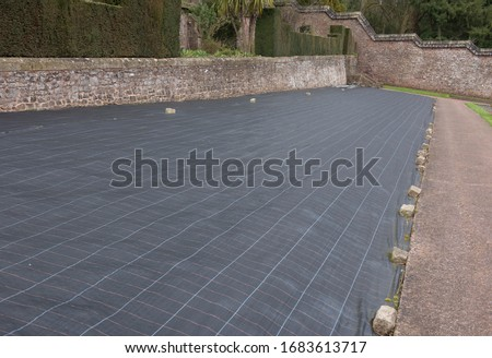 Weed Suppressant Fabric Covering a Bed in a Walled Organic Vegetable Garden in Rural Devon, England, UK Royalty-Free Stock Photo #1683613717