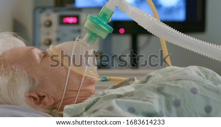 A hospitalized elderly woman attached to a device to help her breathe with an image of the coronavirus in the background. Royalty-Free Stock Photo #1683614233