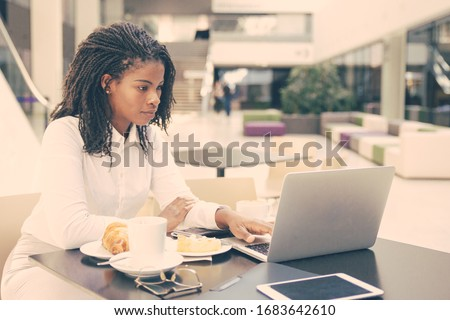 Serious professional watching presentation on laptop during lunch. Young African American business woman drinking coffee in cafe, using computer. Watching content concept #1683642610