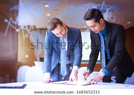 Two partners signing contract with financial analysis graphs. Closeup of content adult businessmen standing at table and signing document in conference room