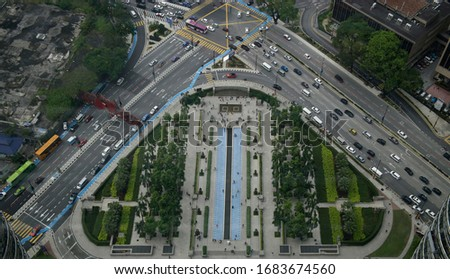 Aerial view of Kuala Lumpur. Traffic in modern city. Street, avenue or highway with cars and buses. Roads in downtown. Urban scenery of garden or park area, fountains, pedestrian sidewalk or footpath. #1683674560