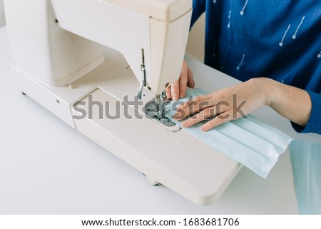 Woman hands using the sewing machine to sew the face medical mask during the coronavirus pandemia. Home made diy protective mask against virus. #1683681706