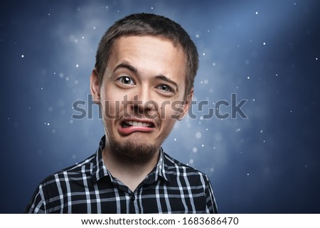 funny guy portrait with funny face expression on blue background