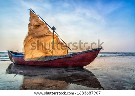 Low angle shot of a sail boat at Nagaon Beach, Konkan...