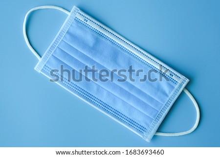 Medical mask on blue background, Coronavirus protection concept. #1683693460