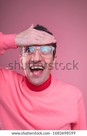 Vertical picture or portrait of young man with weird strange smile posing on camera alone. Hold hand on forehead. Isolated over pink background