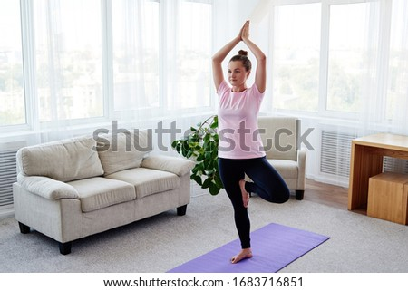 Portrait of young woman practicing balance yoga asana Vrikshasana at home indoor, copy space, back view. Girl doing tree pose, full length. Relaxing and doing yoga. Wellness and healthy lifestyle #1683716851