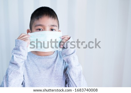 Portrait Asian kid wearing medical mask.A boy wearing mouth mask against air smog pollution. Concept of corona virus quarantine or covid-19.Protection against virus and infection control concept. #1683740008