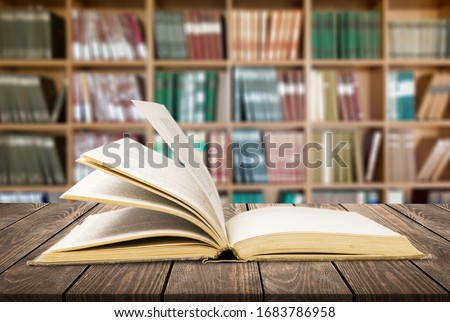 Open book on the desk on the library background. Education concept