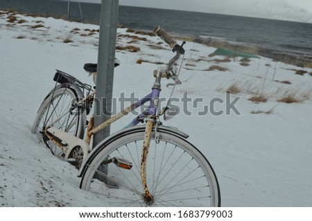 Lonely old and rusty bicycle leaned on a metal rod covered in snow in a snow scenery with lake in the background #1683799003