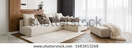 Panorama of elegant and comfortable designed living room with big corner sofa, wooden floor and big windows Royalty-Free Stock Photo #1683813268