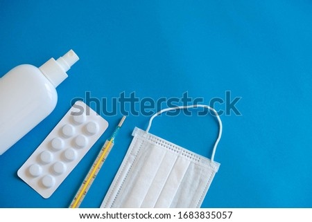 A set of medical disposable mask, antiseptic, pills and a mercury thermometer on a blue background. Medical hygiene and virus protection concept. Top view. Copy, empty space for text #1683835057