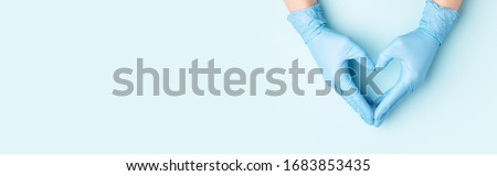 Doctor's hands in medical gloves in shape of heart on blue background. Banner for website with copy space.