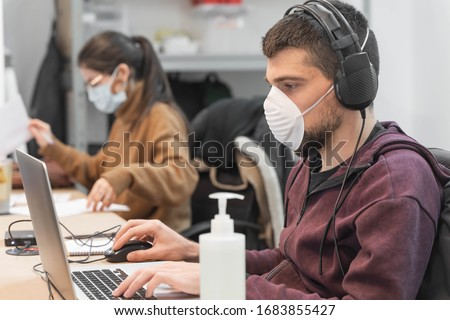 Coronavirus. Business workers working from home wearing protective mask. Small company in quarantine for coronavirus working from home with sanitizer gel. Small company concept. Royalty-Free Stock Photo #1683855427
