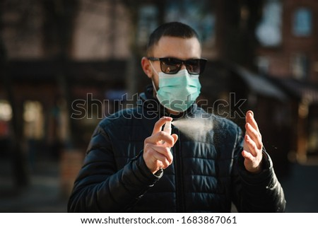 Coronavirus. Cleaning hands with sanitizer spray in city. Man wearing in medical protective mask on street. Sanitizer to prevent Coronavirus, Covid-19, flu. Spray bottle. Virus and illness protection. #1683867061