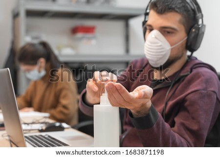 Coronavirus. Business man working from home wearing protective mask and using sanitizer gel. Small company in quarantine for coronavirus working from home with sanitizer gel. Small company concept.  #1683871198
