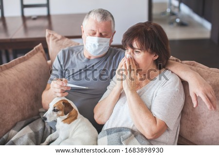 Coronavirus CoVid-19 Couple old aged senior people at home with seasonal winter cold illness disease sit down on the sofa. Elderly couple in medical masks during the pandemic Royalty-Free Stock Photo #1683898930