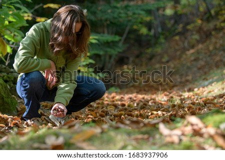 Woman portrait in the middle of the countryside while collecting chestnuts #1683937906