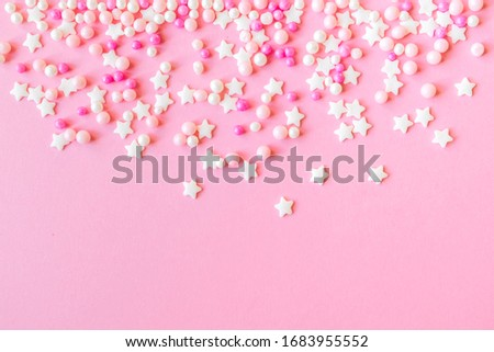 Festive frame made of colorful pastel sprinkles on a pink background, copy space on top. Sprinkle sugar with balls and stars, decoration for cake and bakery products. Top view or flat lay Royalty-Free Stock Photo #1683955552