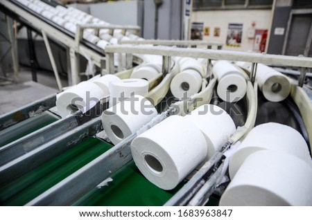 Production of Toilet paper in factory. Toilet paper rolls making machine. Tissue and Kitchen Towels Machine. Long conveyor with toilet paper moving on.  Royalty-Free Stock Photo #1683963847