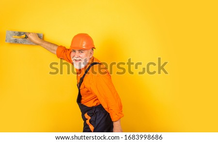 man with spatula. process of applying layer of putty. Plastering tools for plaster. plaster trowel spatula on yellow drywall plasterboard. Plasterer in working uniform plastering wall indoor. #1683998686