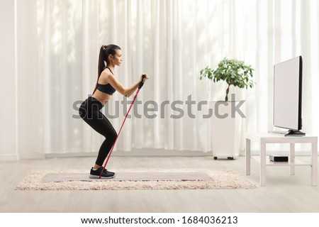 Young woman in sportswear exercising with a resistance band in front of a tv at home #1684036213