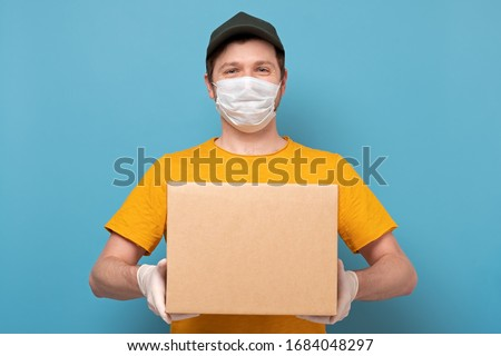 Young delivery man in nedical mask holding and carrying a cardbox isolated on blue background. Buy food online in quarantine concept. #1684048297