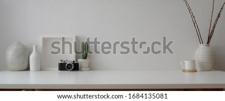 Cropped shot of minimal workspace with camera, decorations and copy space on white table with white wall
