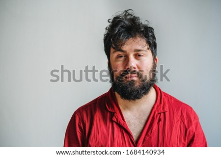 Sleepy man with messy hair and pyjamas, tired mand with beard looking in the camera with white background, sleepless guy feeling exhausted Royalty-Free Stock Photo #1684140934