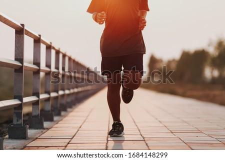 Runner feet running on road closeup on shoe. MAN fitness sunrise jog workout welness concept. #1684148299