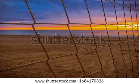 Volleyball net against the backdrop of a stunning fiery sunrise on the beach with sea views #1684170826