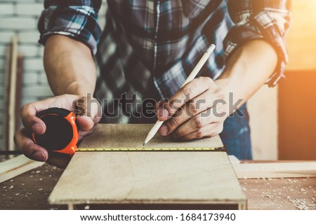 Carpenter working on wood craft at workshop to produce construction material or wooden furniture. The young Asian carpenter use professional tools for crafting. DIY maker and carpentry work concept. #1684173940