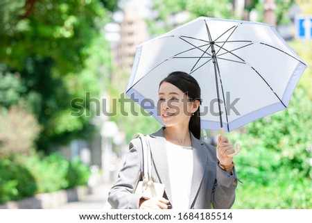 Business woman in suit with parasol Royalty-Free Stock Photo #1684185514