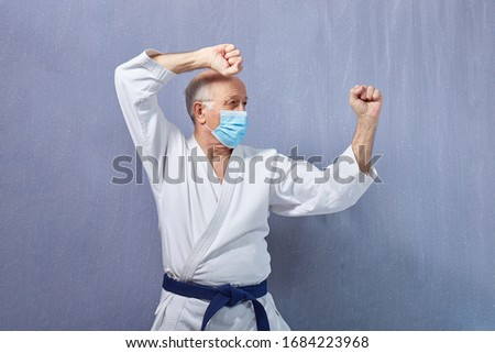 In a medical mask and karategi, an old man trains a punch  Royalty-Free Stock Photo #1684223968