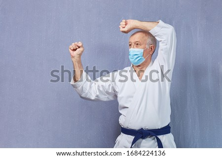 In a medical mask and karategi, an old man performs blocks with his hands Royalty-Free Stock Photo #1684224136