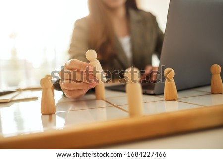 Businesswoman leader choosing wooden people from a group of employees on a planning board #1684227466