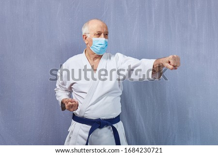 In medical mask, an old man in karategi beats a punch Royalty-Free Stock Photo #1684230721