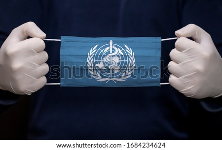 Health employee doctor holding medical face mask with WHO (World Health Organization) flag. Coronavirus (COVID-19) pandemic affects the country.  Royalty-Free Stock Photo #1684234624