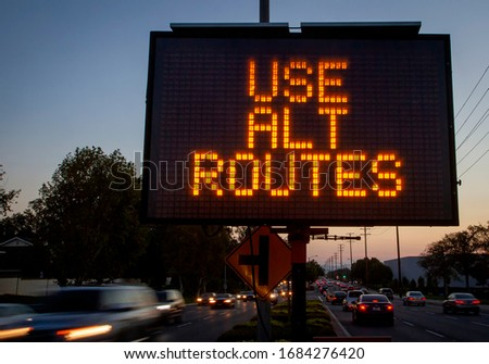 Electronic traffic sign stating Use Alternate Routes with blurred traffic