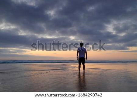Silhouette of a man standing on the beach on a cloudy morning watching the sunrise. Royalty-Free Stock Photo #1684290742