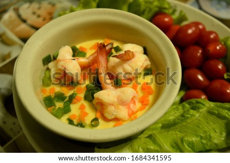 this pic show steamed egg with shrimp and vegetable on table