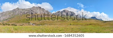 Wide panorama of grass fields, Andringitra massif tall rocky mountains in distance, blue sky above. Typical scenery seen during trek to Pic Boby peak