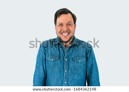 Portrait of young man smiling and looking at camera with one eyebrow raised. Denim shirt and isolated white background.