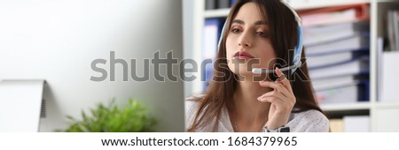 Portrait of lovely young woman wearing headset and answering questions on computer. Call center operator working in office. Folders on background. Telemarketing concept #1684379965
