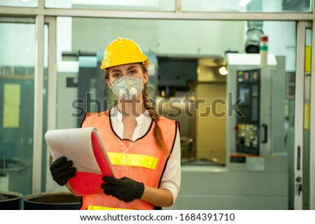 Female Mechanic wearing  protective mask to Protect Against Covid-19,Female technician worker working and checking machine in a large industrial factory,Coronavirus has turned into a global emergency #1684391710