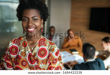 close up of beautiful young smiling professional black african business woman, coworkers hold a meeting in background Royalty-Free Stock Photo #1684422238