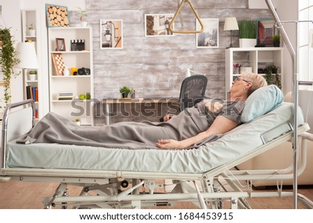 Picture old woman resting in bed in a nursing room. Peaceful pensioner.