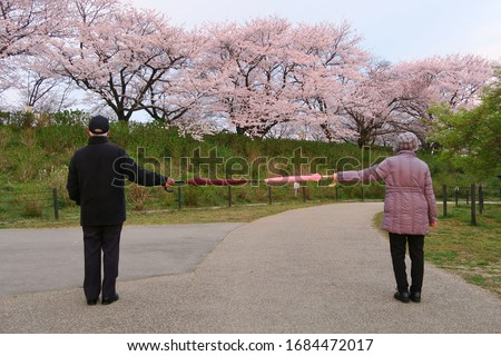 Social distancing (6 feet / 2 meters) to avoid the spread of coronavirus (COVID-19). Two people stand apart holding two umbrellas. A new concept along with elbow bumping. #1684472017