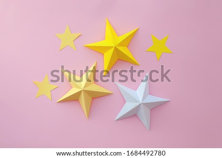 Handmade paper art and cut white and yellow stars on pink background.