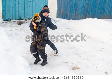Two little European boys play and fight in the snow in winter.